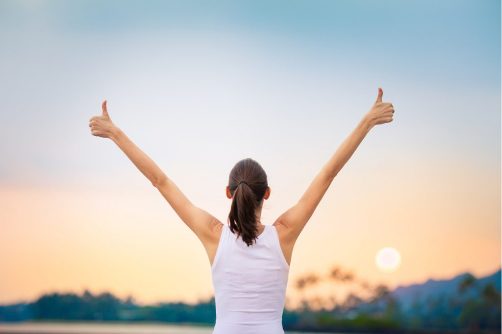 Woman facing the sunset with both hands raised, showing a winning attitude.