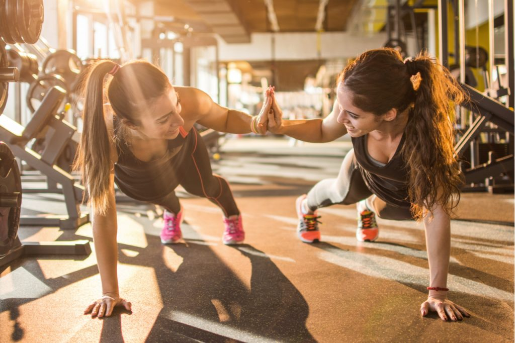 Sporty women giving high five to each other while working out together at gym.
