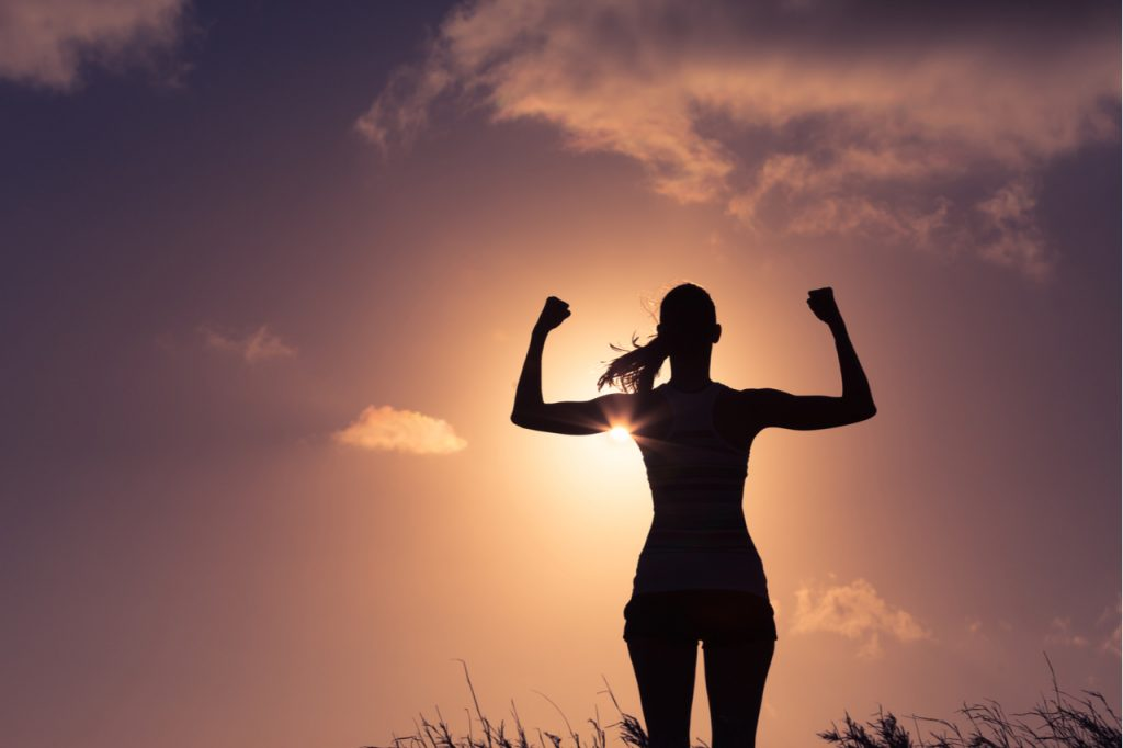 A silhouette of a woman flexing her arms. Visualize your Goals to achieve them.