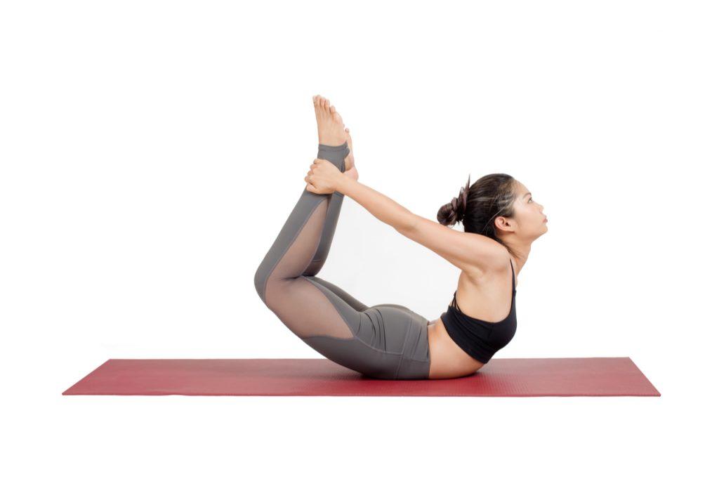 An asian woman doing the dhanurasana yoga pose.