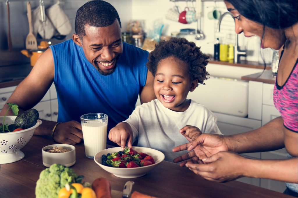 An African American family enjoying a bowl of berries in their kitchen with seasonal fruits and vegetables on their table.