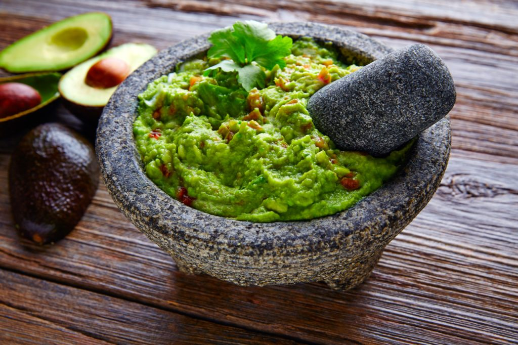 A bowl of guacamole and sliced avocados on the side.