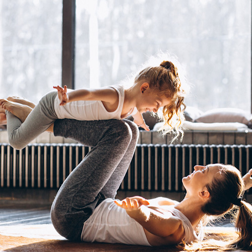 A kid riding her mother's legs while she's working out with her.