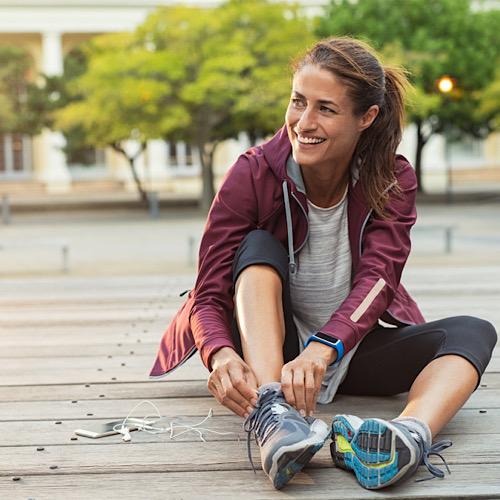 Cheerful runner sitting on floor on city streets