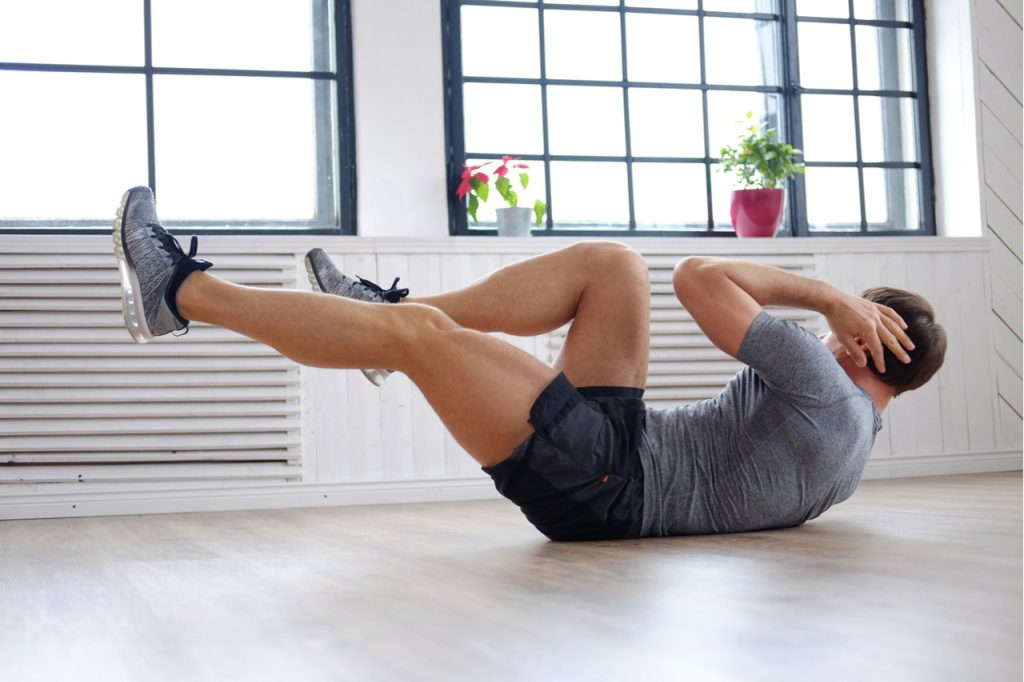 Athletic man doing stomach workouts at home.