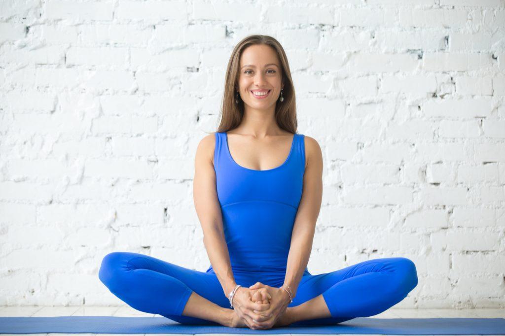 A woman wearing all blue clothing doing the baddha konasana yoga pose.