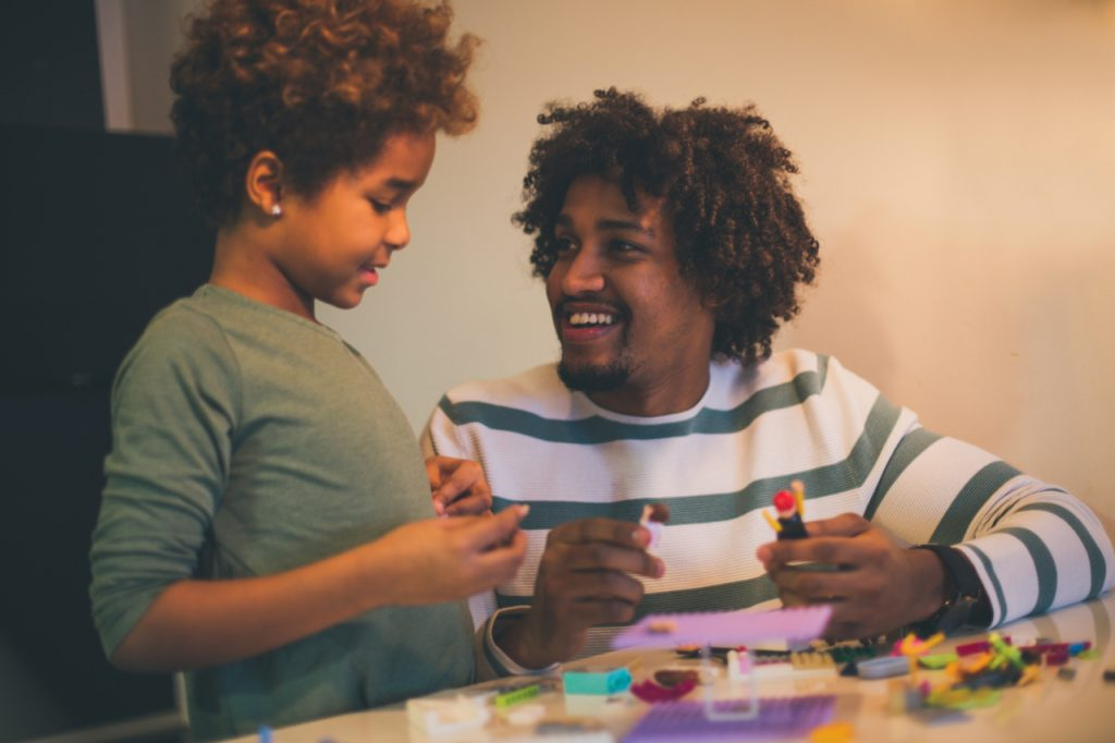 African American father and daughter playing with cubes.