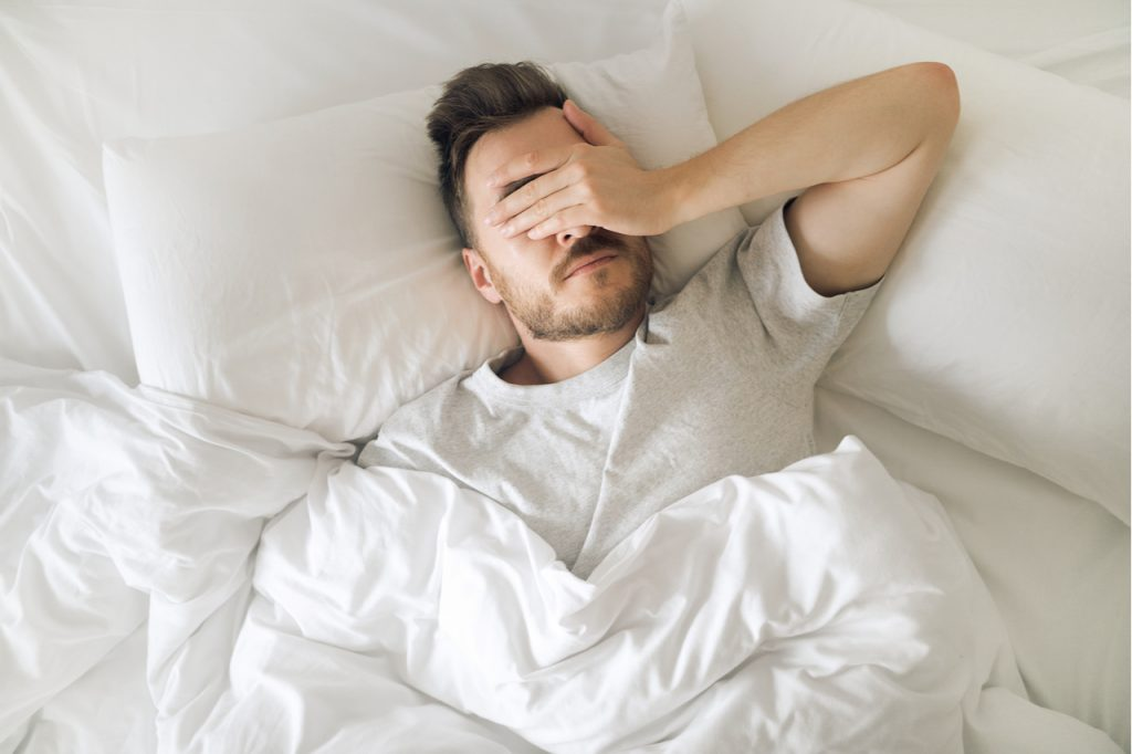 Tired young man in bed closing his eyes and can't sleep due to lighting.