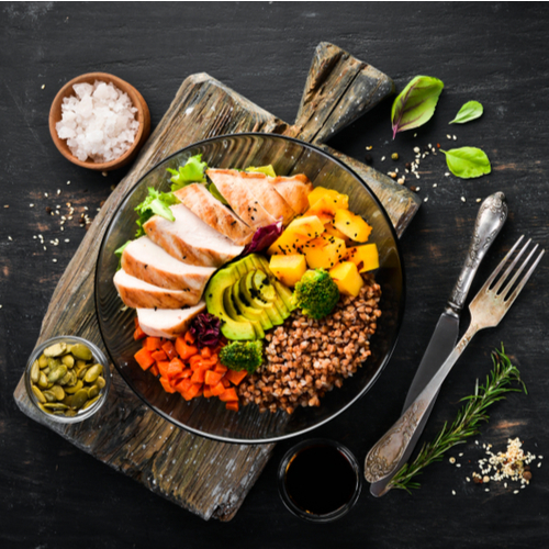 Buckwheat, pumpkin, chicken fillet, avocado, carrots on a black background.