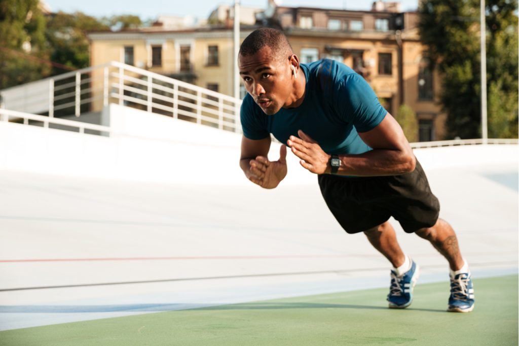 A fit man doing clap push-ups on a track field.