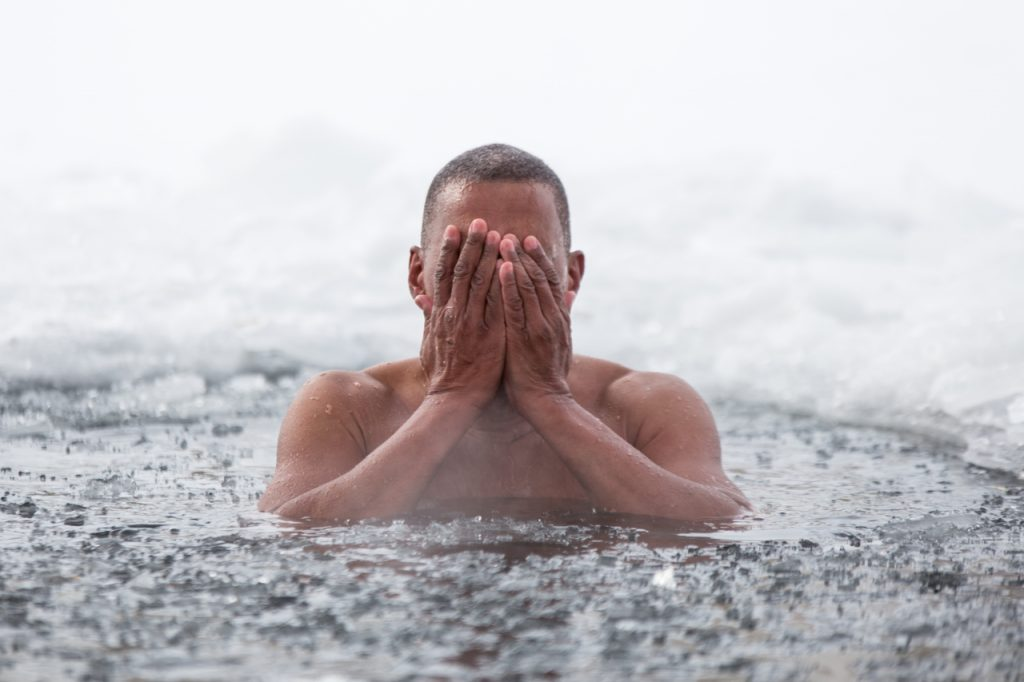 Man swims in an ice hole in winter called the polar bear plunge.