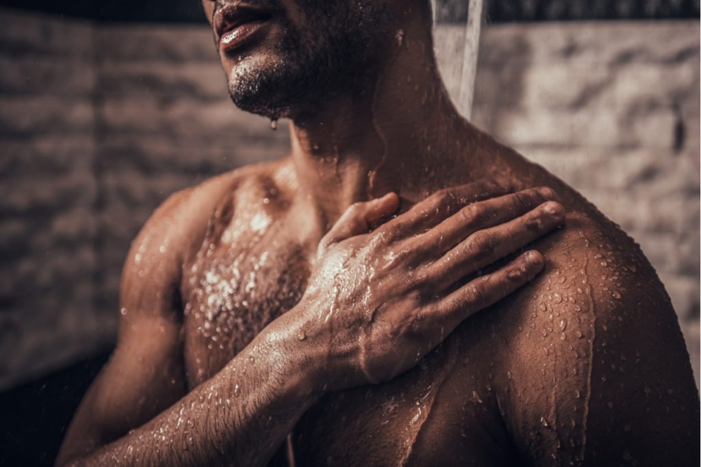 Man taking cold shower in bathroom at morning.
