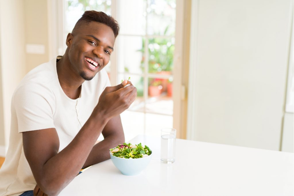 Man eating a healthy vegetable salad using a fork to eat lettuce, happy and smiling sitting on the table