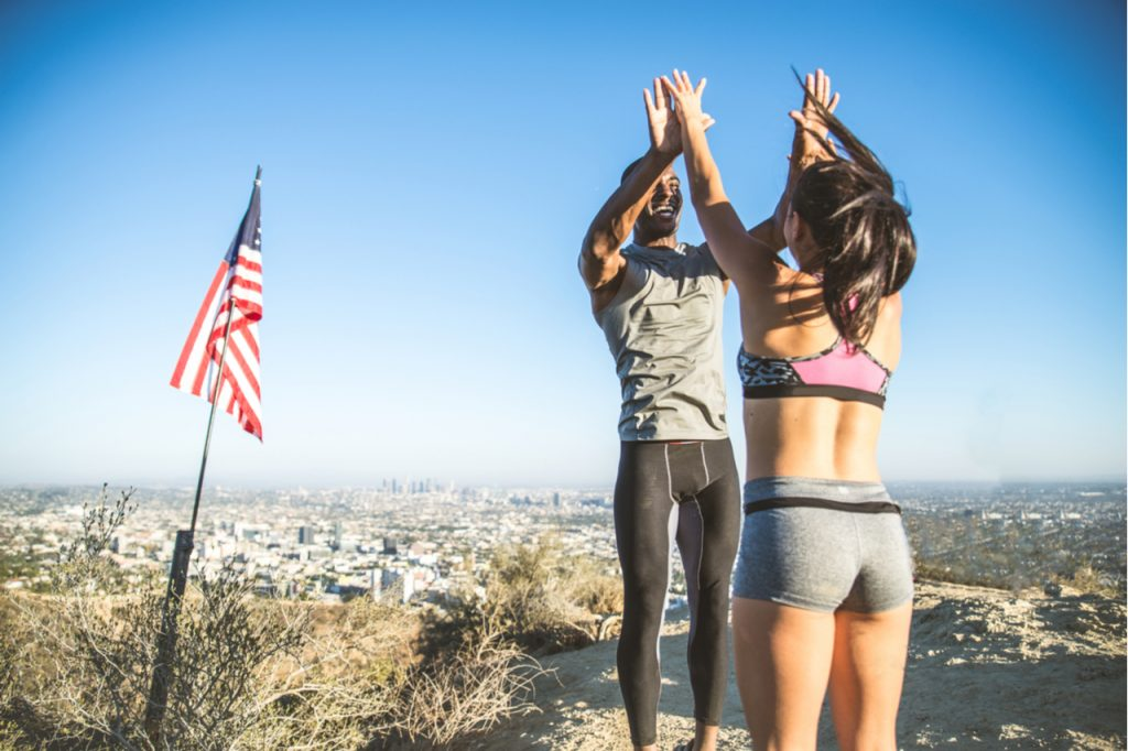 Happy looking couple with their hands up, next to an american flag celebrating memorial day 2020 right after a successful jog or run.