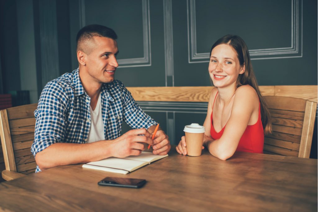 Couple talking and journaling over coffee happily.