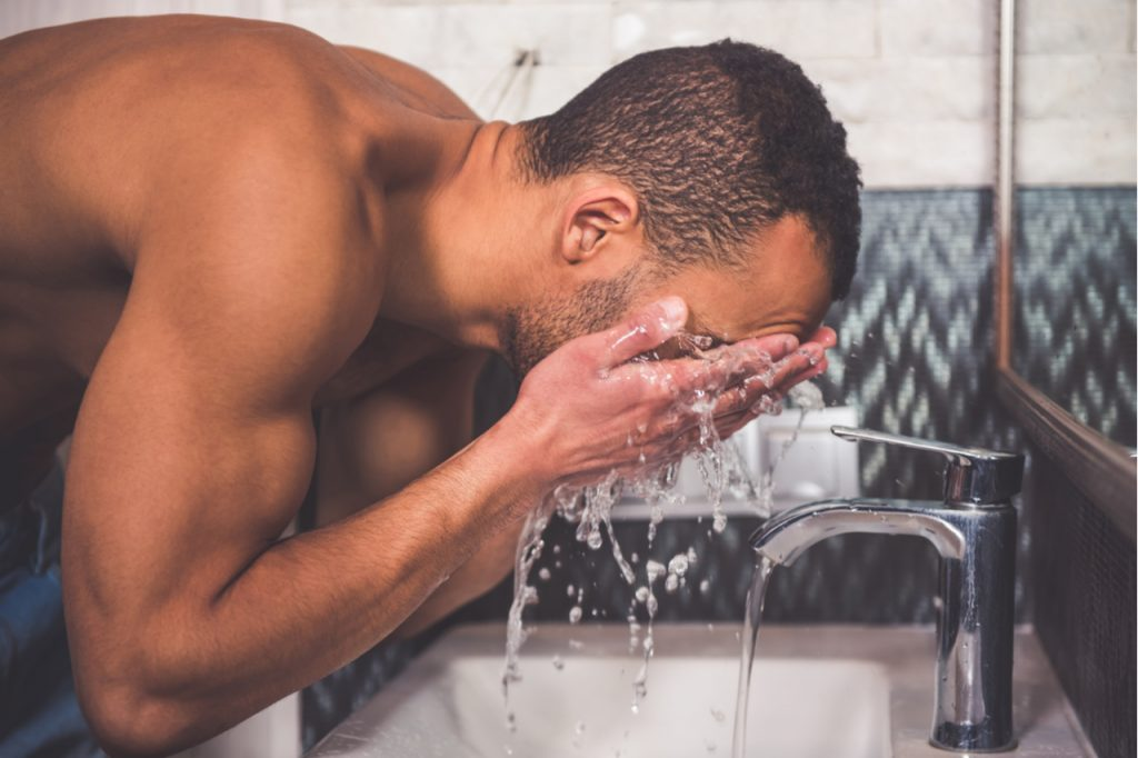 Man washing himself in bathroom as a daily routine part of mental health first aid.