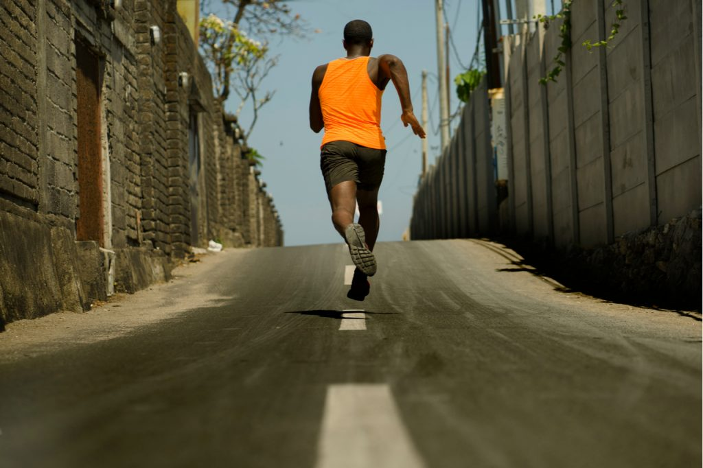 Back view of athletic professional sport man running training hard outdoors on asphalt road.