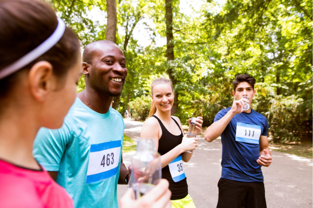 Group of young athletes drinking water after running.