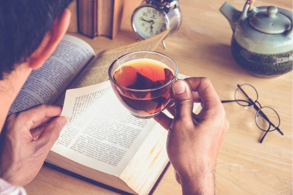 A man reading books and drinking tea