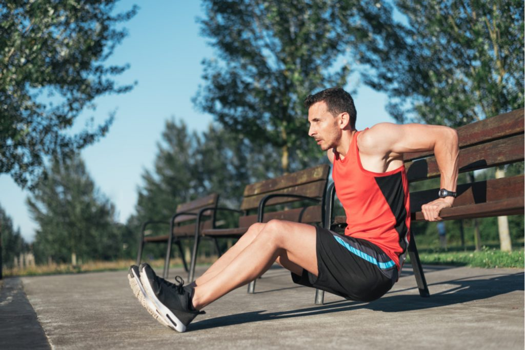 Fitness man doing bench triceps dips during workouts for outside cross training workout.