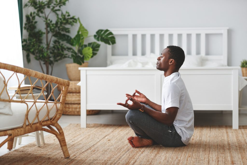 Man doing yoga and sitting in lotus position at home in the bedroom.