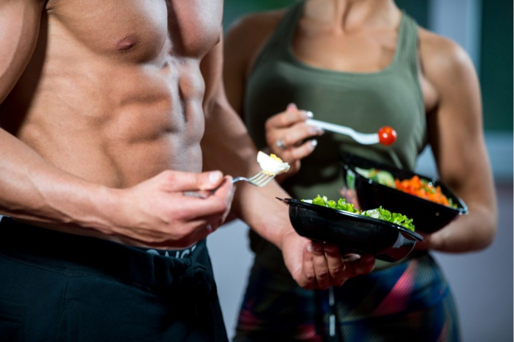 Happy couple in gym feeding each other with fresh salad at gym.