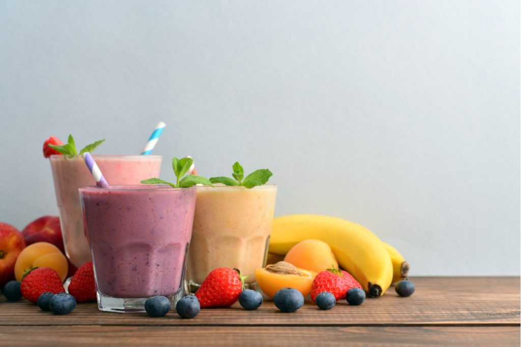 Three different glasses of  fruit smoothies with a variety of fruits and berries on the glass footing.