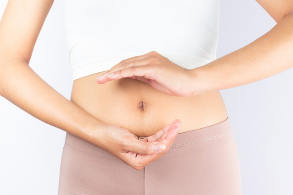 A woman forming a circle with her hands in front of her stomach which supposedly means that she has good digestive system function.