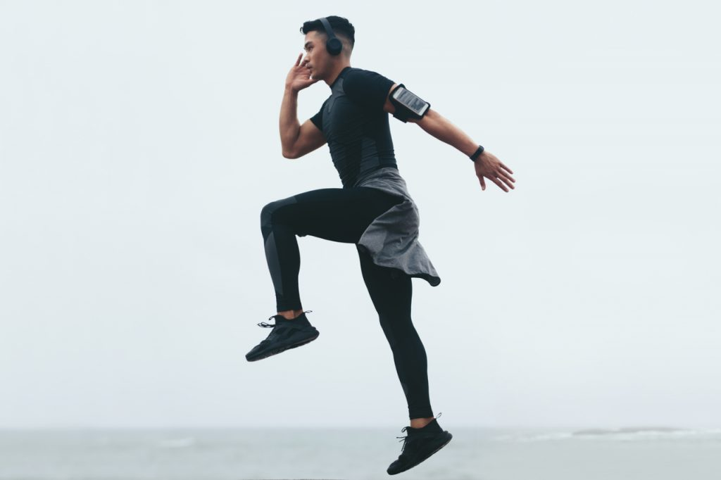 Sporty asian man doing jump lunges.