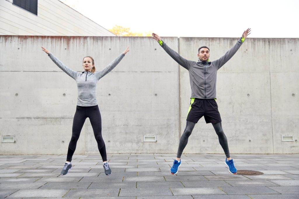 Couple doing jumping jacks to start their full body workout at home.