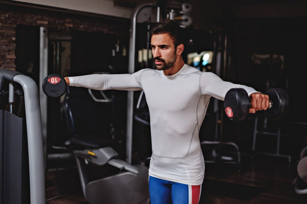 Man doing lateral arm raise with a dumbbell.