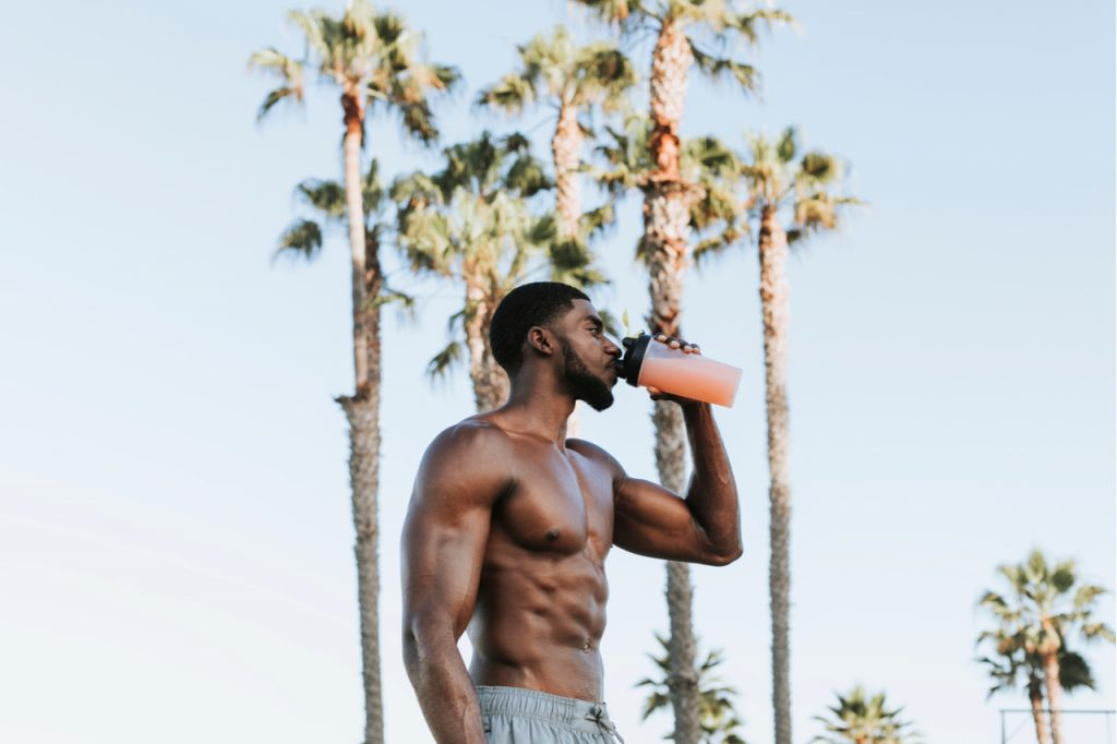 A shirtless man drinking creatine monohydrate shake outdoors with palm trees in the background.