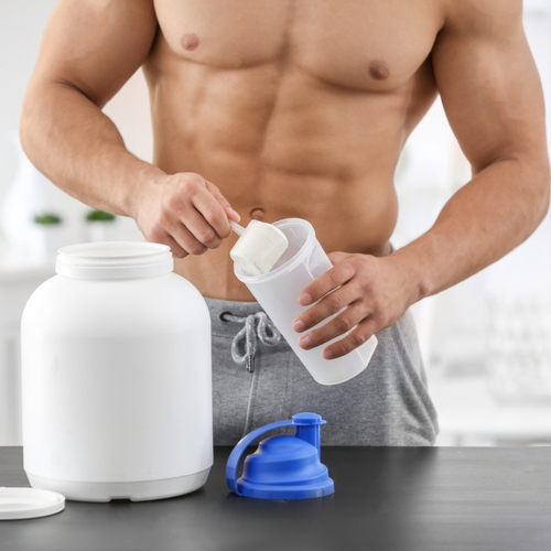 A shirtless man making protein shake.