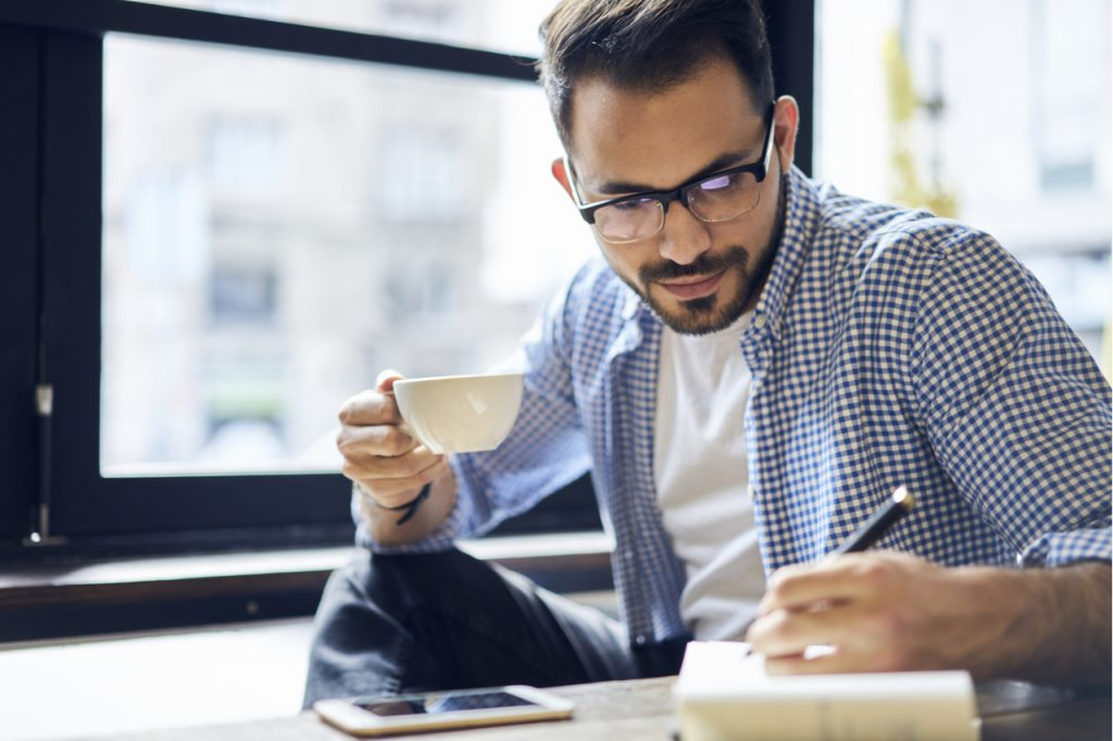 A man holding a cup of coffee while writing a meal plan.