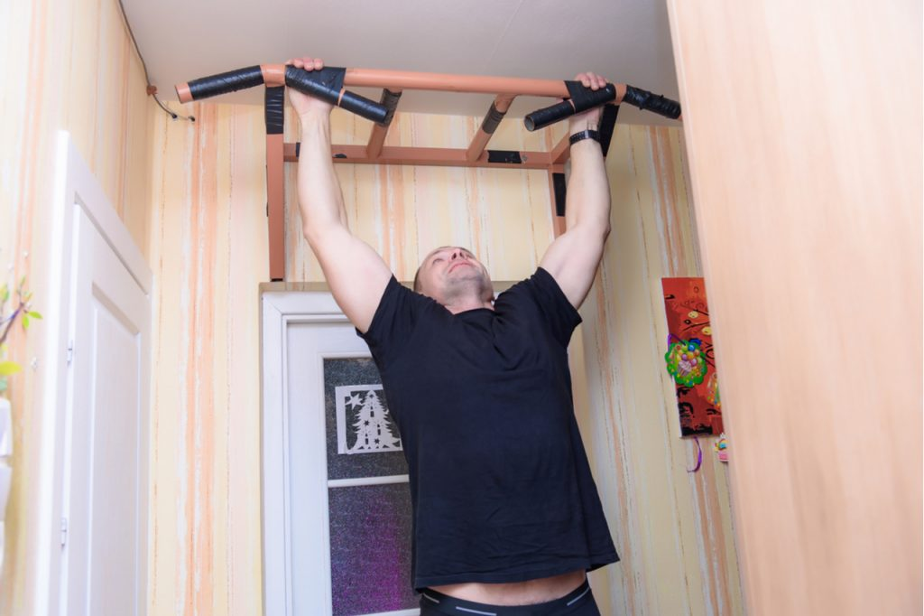 A man doing pull ups at home.