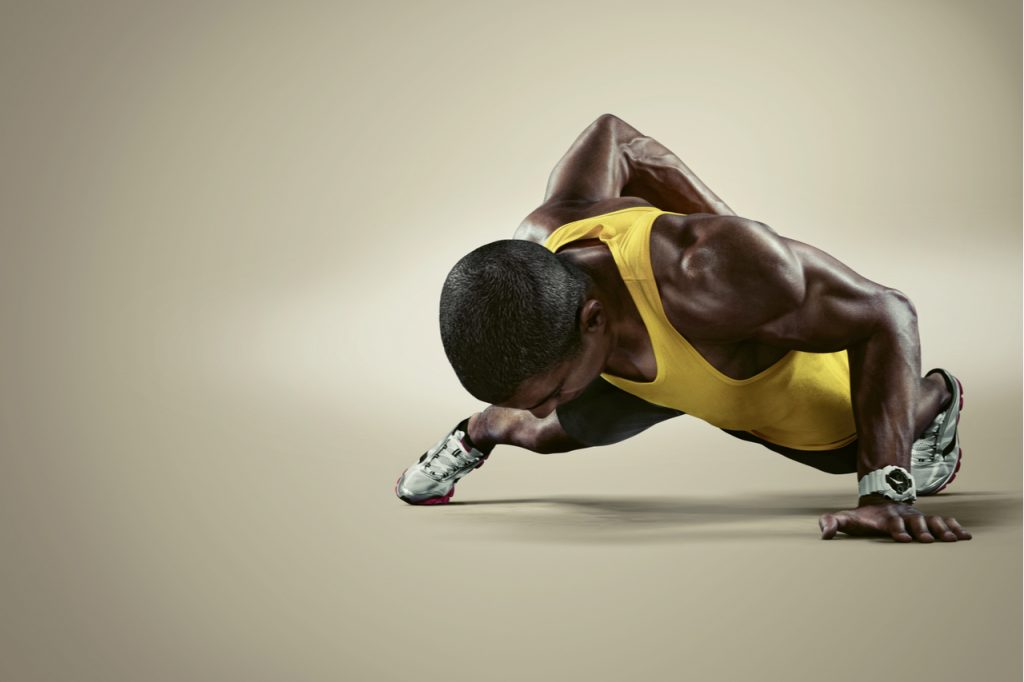 Young athletic man doing push-ups.