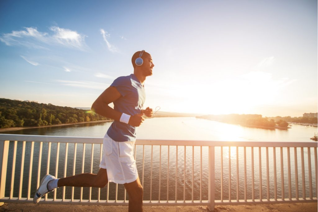 A man doing an early jogging at a bridge as part of his healthy habits.
