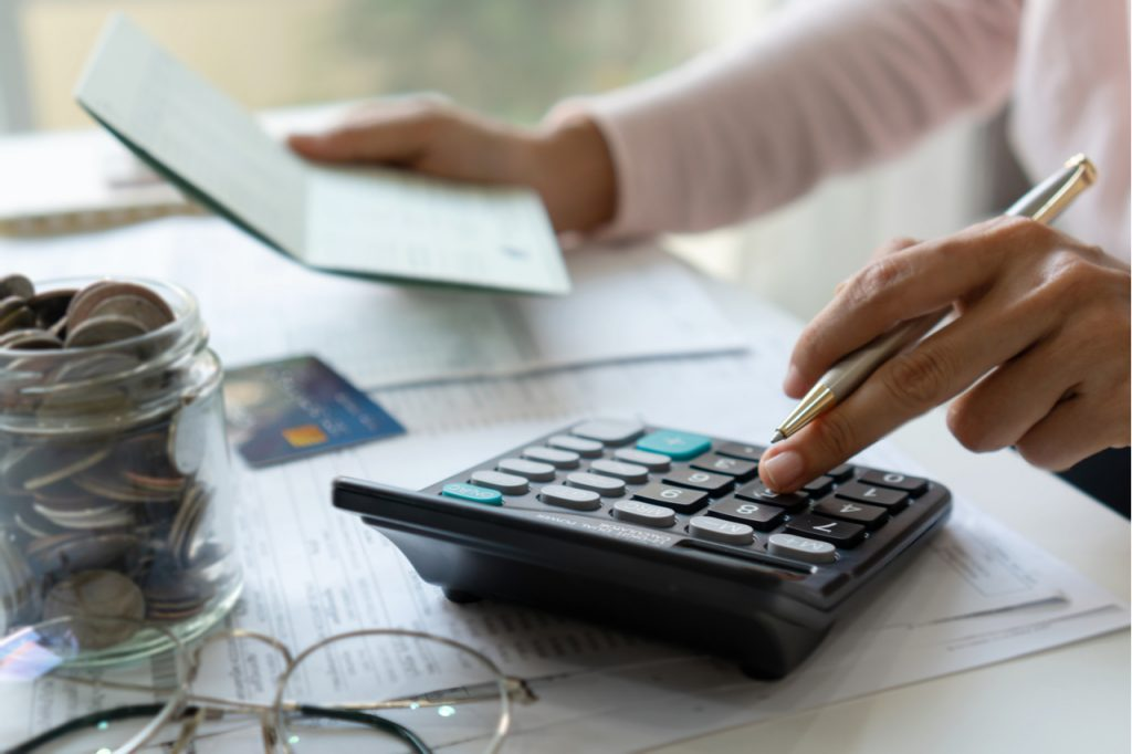Woman checking bills, taxes, bank account balance and calculating credit card expenses.