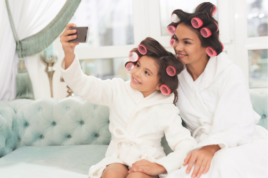 Mother and daughter in white bathrobes are sitting on the couch taking selfie.