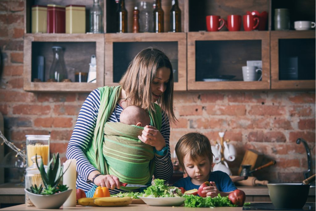 Mom and adorable boy and baby in sling cooking together in a sunny kitchen.