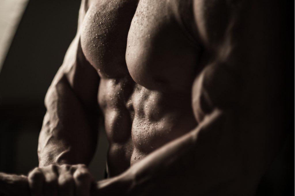 Sweaty muscular man flexing his muscles.