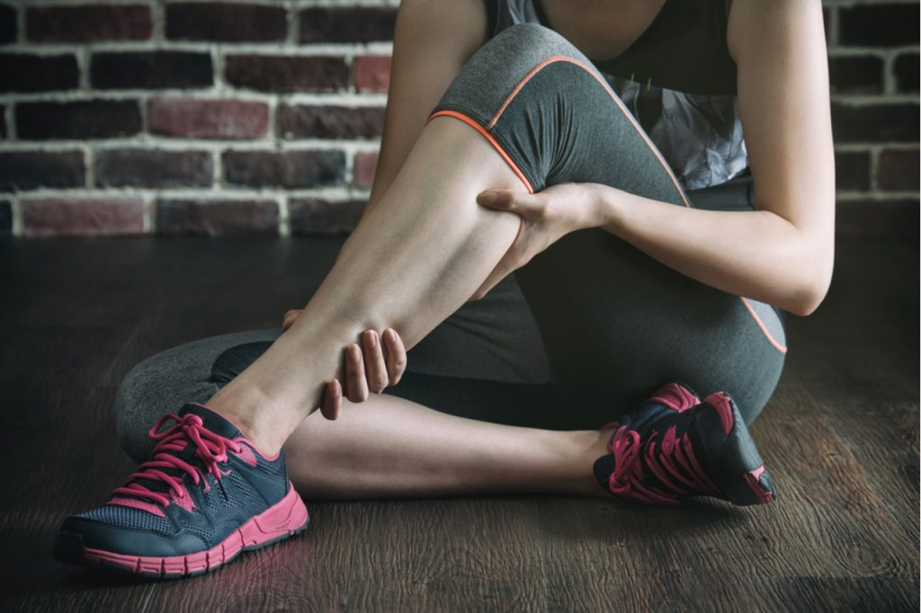 Woman in fitness exercise training needing to recover from muscle soreness.