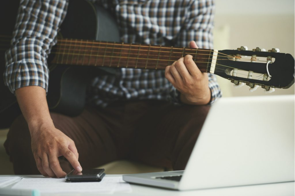 Man writing notes in his smartphone when playing guitar at home.