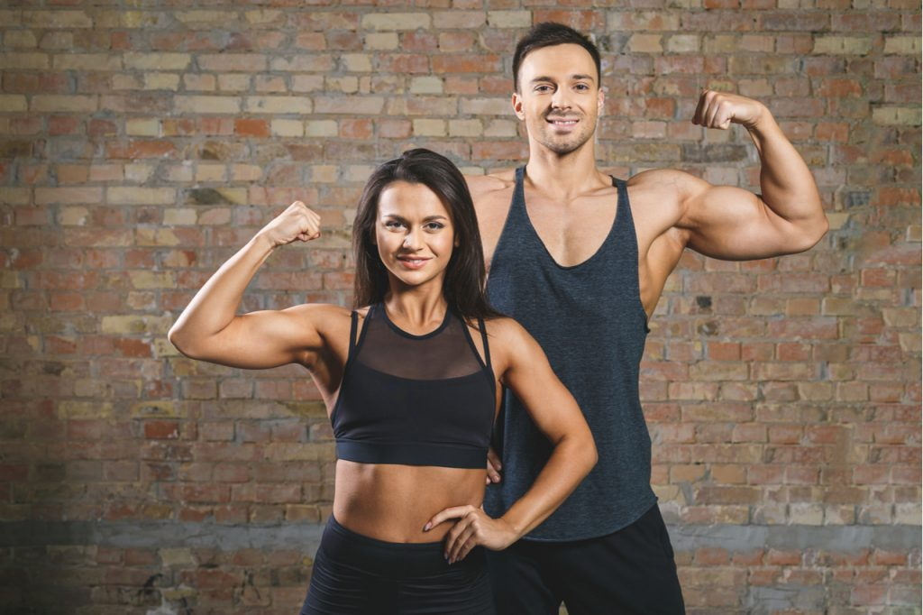 A man and a woman flexing their arm muscles showing that they are physically fit.