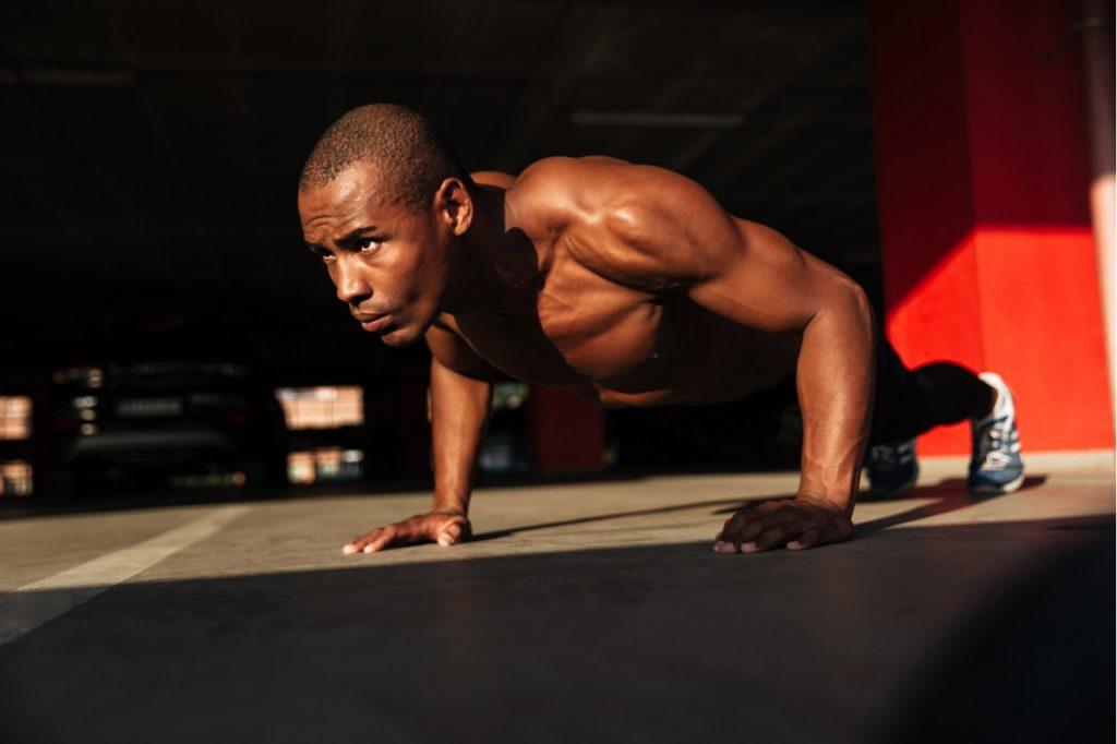 Close up portrait of a sportsman doing push ups indoors.