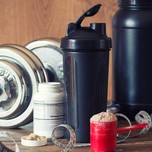 Supplements in powder and capsule, plastic shaker and tape measure on wooden background.