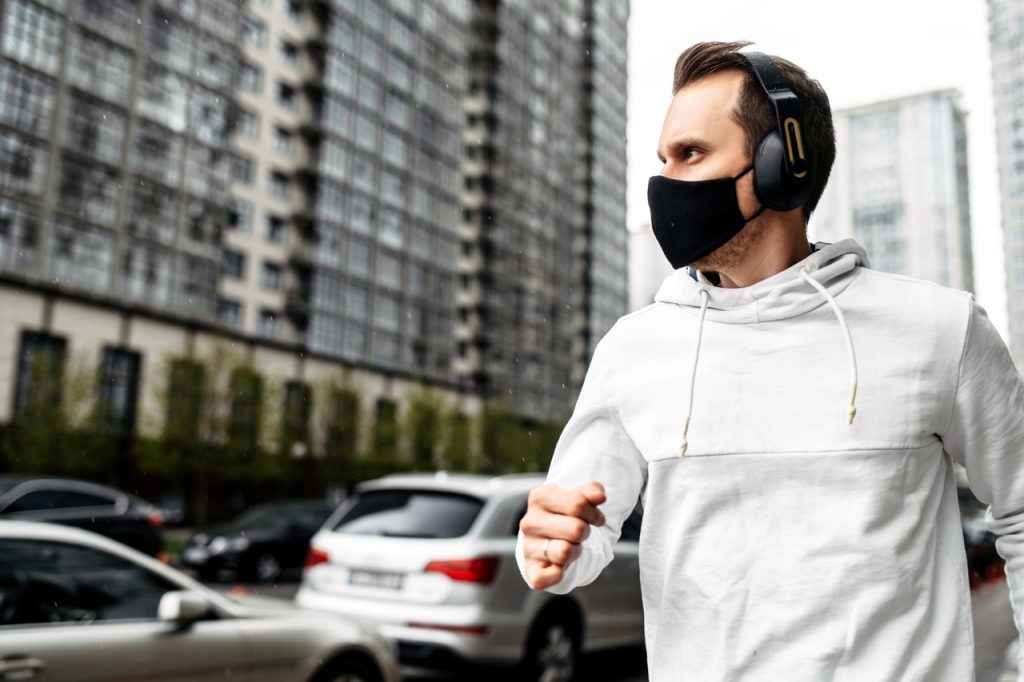 Man is jogging in a protective mask among high-rise buildings.