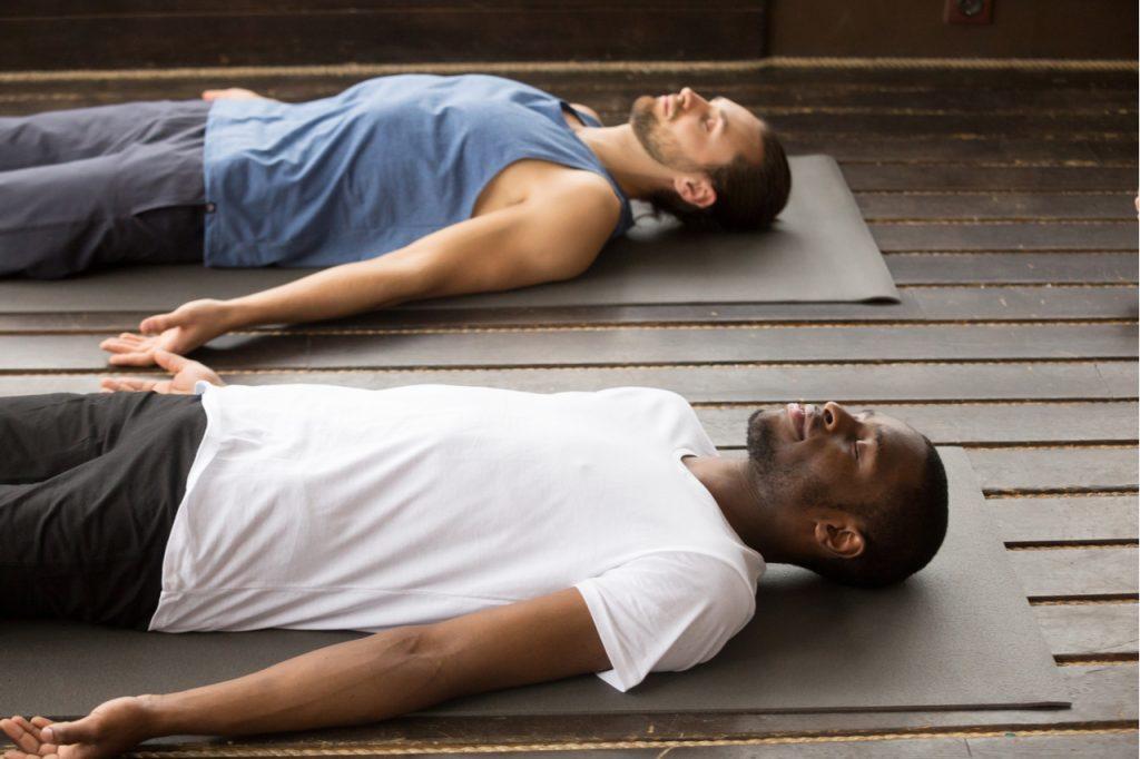 Two men doing the savasana yoga pose.