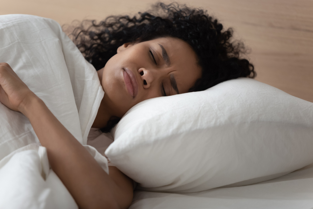 Close up african woman lying in bed has nightmares bad sleeping