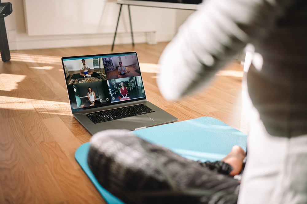 woman conducting virtual fitness class with group of people